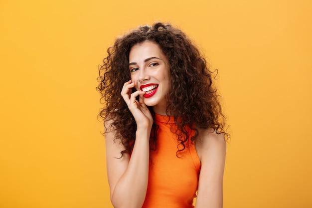 Mezzo busto di affascinante donna femminile sciocca e spensierata con l'acconciatura riccia in top corto che morde il dito e sorride sensualmente e civettuola alla macchina fotografica cercando sexy e audace su sfondo arancione.