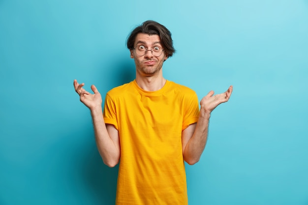 Waist up shot of clueless brunet european man shrugs shoulders raises palms feels doubtful