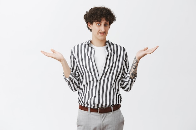 Waist-up shot of clueless good-looking and funny unaware guy with moustache and curly dark hair shrugging with spread palms having no idea feeling uncertain how to act or what answer