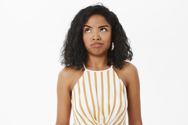 Waist-up shot of clueless and questioned silly african american girl trying understand what made