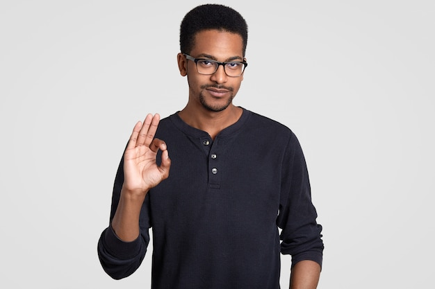 Waist up shot of confident dark skinned man shows approval gesture