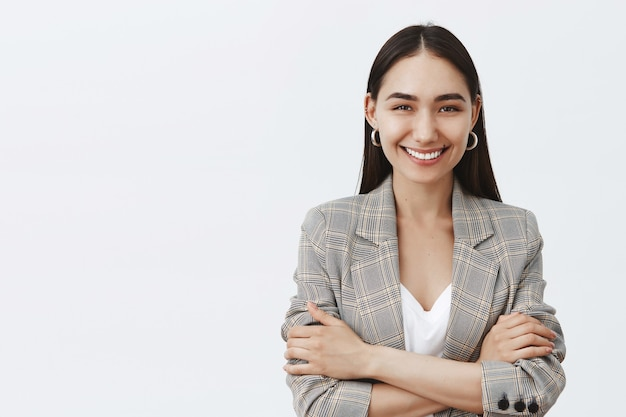 Waist-up shot of confident happy female entrepreneur in stylish jacket over t-shirt, holding hands crossed on chest in self-assured pose, smiling broadly, knowing how help any customer