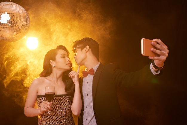 Waist up shot of couple in fancy clothing giving a kiss for selfie at a party