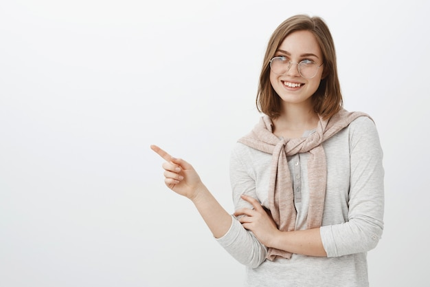 Waist-up shot of creative attractive brunette female coworker in glasses and pullover tied over neck gazing and pointing left