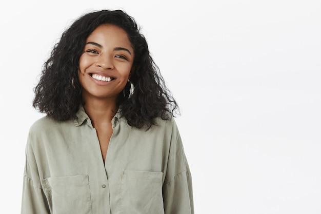Waist-up shot of cute friendly-looking pleasant african american female