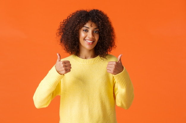 Waist-up shot cute supportive african-american woman feeling happy about great idea, shot thumb-up and smiling, agree with you, give positive answer, recommend product, orange wall