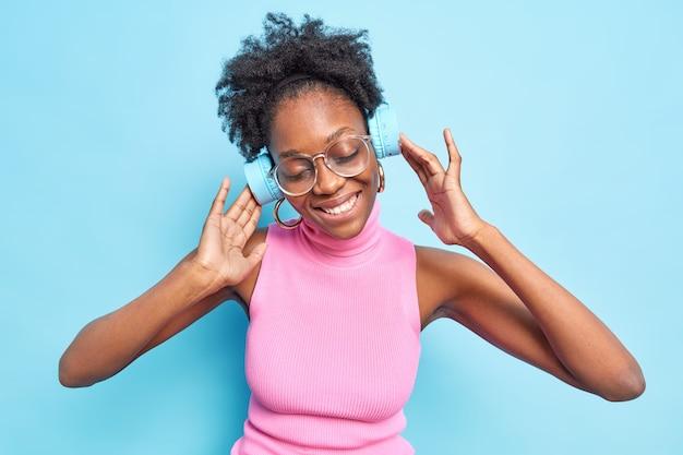 Waist up shot of dark skinned woman with curly hair enjoys listening music via stereo wireless headphones