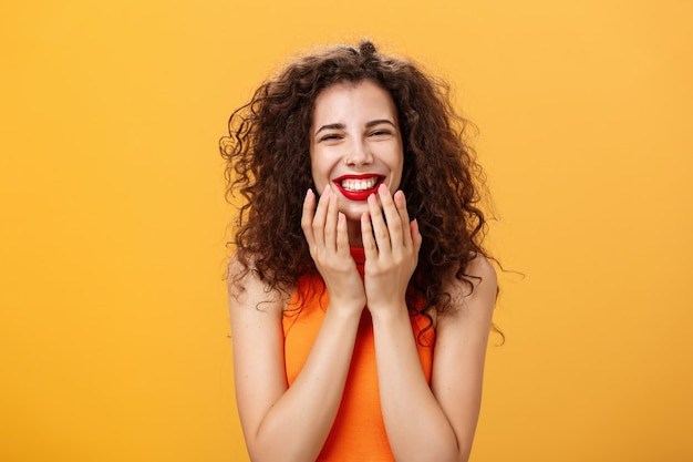 Waist-up shot of delighted charming and cute curly-haired caucasian female in cropped top being touched with sweet words smiling pleased holding palms on jaw-line surprised and happy over orange wall.