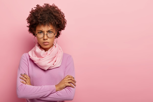 Waist up shot of displeased afro woman wears round spectacles, long sleeved sweater, keeps arms folded