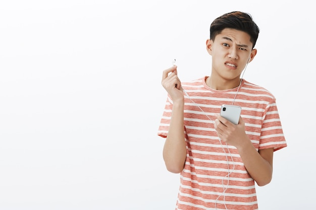 Waist-up shot of displeased cute young asian boy in striped t-shirt taking off broken earbud holding smartphone frowning dissatisfied and bothered with law quality of sound