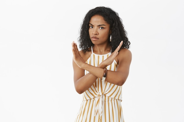 Waist-up shot of displeased dissatisfied serious-looking dark-skinned girl with curly hairstyle crossing arms on body