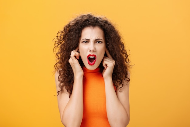 Waist-up shot of displeased intense and unsure female with curly hairstyle in orange top closing ears with fingers frowning asking repeat question while standing in loud noisy place over orange wall.