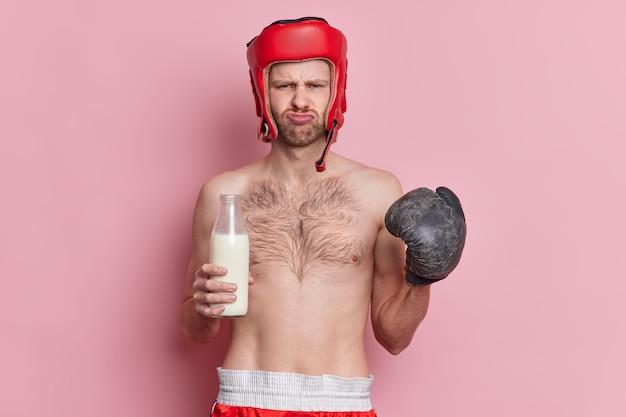 Mezzo busto di sportivo in topless dispiaciuto tiene una bottiglia di vetro di latte si sente stanco di allenarsi e di fare sport indossa guanti da boxe casco protettivo sulla testa