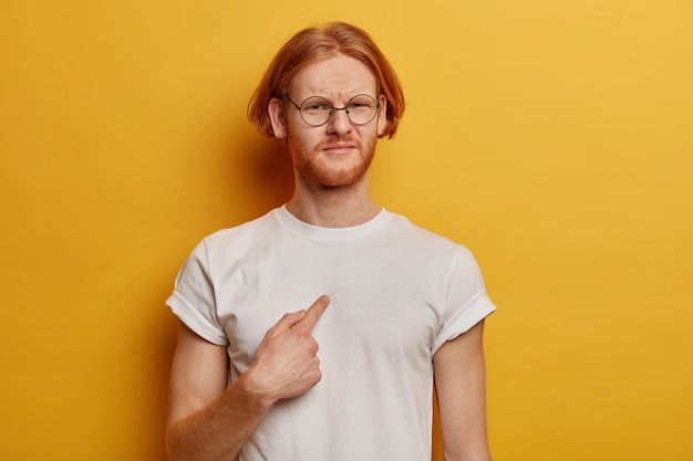 Waist up shot of dissatisfied bearded man with ginger bob hairstyle points at himself, asks why me, wears casual white t shirt, spectacles, poses against yellow  wall, being bothered and unhappy