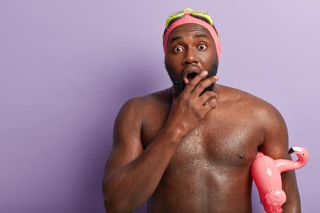 Il colpo alla vita di un ragazzo dalla pelle scura imbarazzato apre ampiamente la bocca, ha un corpo muscoloso, nuota in piscina