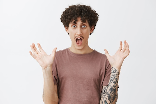 Waist-up shot of emotive pleased and excited man being under impression shaping something big with hands while describing amazing story opening mouth and staring surprised and thrilled