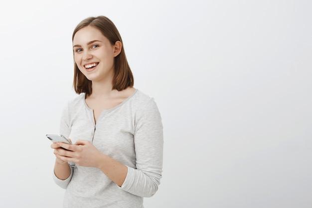 Mezzo colpo di donna bruna energica creativa e dall'aspetto amichevole felice in camicetta casual in piedi mezzo capovolto sul muro grigio che tiene smartphone ridendo essendo intrattenuto e divertito