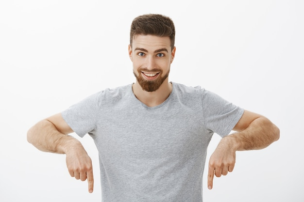Waist-up shot of excited and confident charming brunet man with beard and moustache pointing down and smiling broadly looking with enthusiasm and excited expression against grey wall