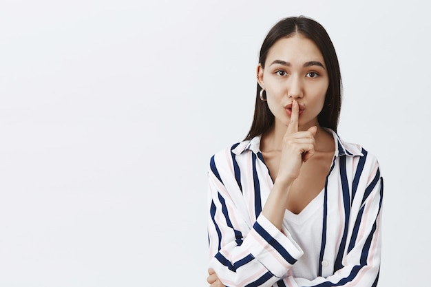 Waist-up shot of fashionable attractive woman in striped blouse, folding lips and saying shhh while making shush gesture with index finger over mouth, keeping secret or telling rumor