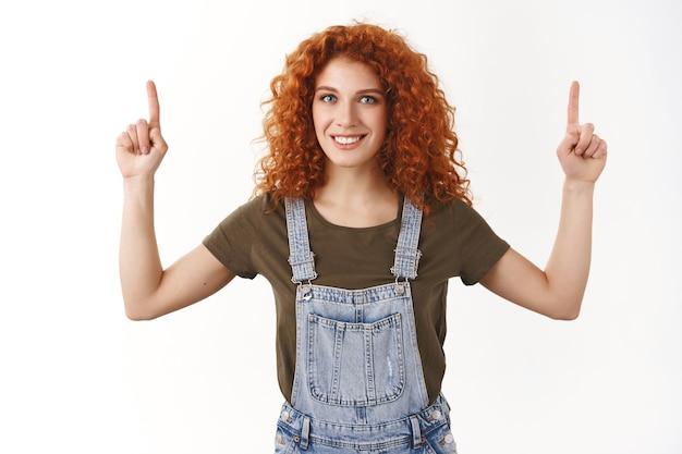 Подняв талию дружелюбную амбициозную рыжую кудрявую женщину демонстрирует промо верха, показывает вверх, радостно улыбается, представляет рекламу, стоит у белой стены в джинсовом комбинезоне и футболке