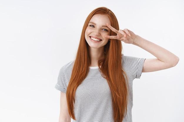 ウエストアップショットフレンドリーな種類楽観的な魅力的な若い幸運な10代の赤毛の少女青い目傾斜頭笑顔白い歯ショー勝利平和ジェスチャーお楽しみパーティー、立っている白い壁