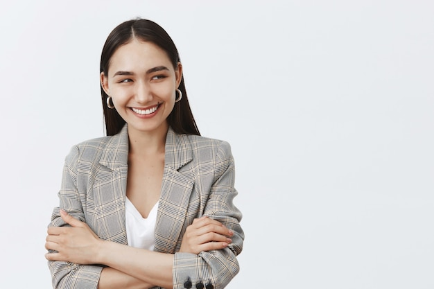 Waist-up shot of good-looking bright female in jacket and earrings, looking right and smiling broadly, holding hands crossed on chest, chuckling, having fun in team circle during business meeting