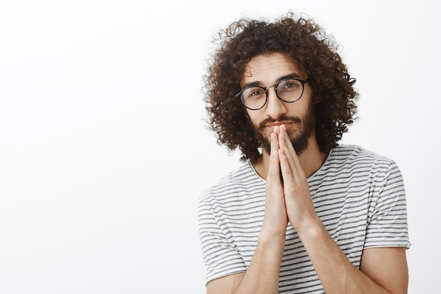 Waist-up shot of handsome dreamy hispanic male model with beard and afro hairstyle, holding hands in pray near mouth and gazing thoughtfully