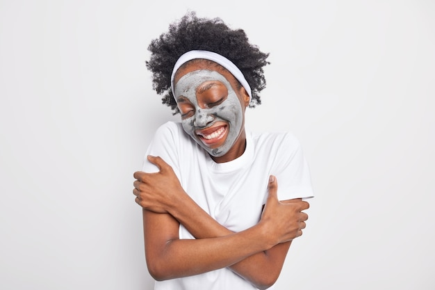 Waist up shot of happy afro american woman embraces herself recalls nice memories keeps eyes shut applies clay moisturizing mask for skin care