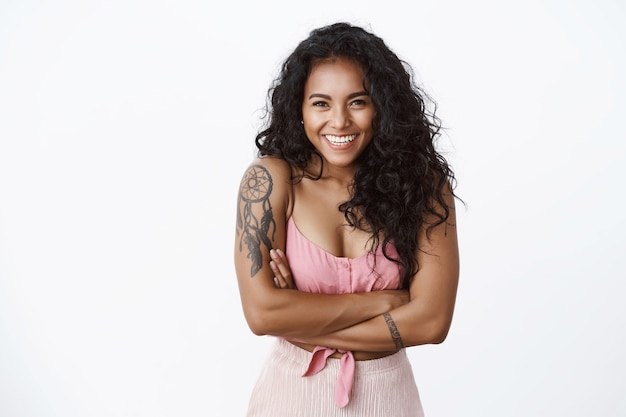 Waist-up shot happy carefree attractive curly-haired girl with tattooed arms, toothy white smile, cross hands chest and gazing camera enthusiastic, standing white wall