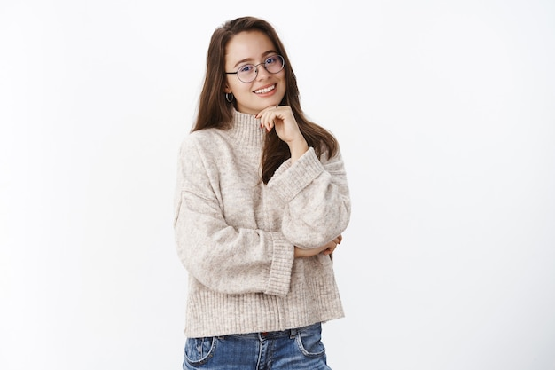 Waist-up shot of happy charismatic young brunette in glasses and warm sweater tilting head and smiling holding hand on chin, crossing arm against chest having conversation over gray wall.