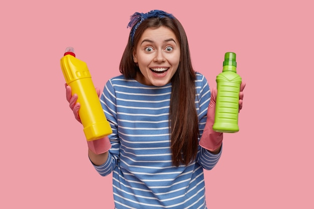 Waist up shot of happy european woman with cheerful expression wears striped clothes, carries bottles with cleaning supplies
