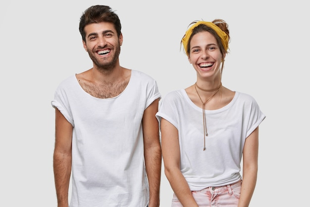 Waist up shot of happy female and male fellows dressed in white mockup t shirt, smile broadly, being in high spirit, stand closely to each other, isolated over  wall