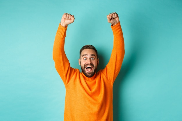 Waist-up shot of happy guy celebrating victory, rejoicing of winning a bet, achieve goal and smiling satisfied, shouting yes, standing over light blue background.