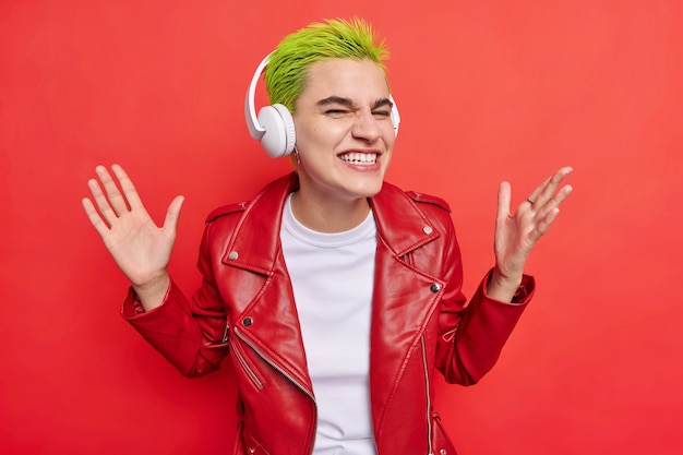 Waist up shot of happy hipster girl clenches teeth smiles gladfully at front has fun while listening music in headphones wears leather jacket isolated over bright red wall