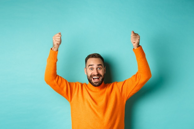 Waist-up shot of happy man raising hands as if holding a sign, showing logo or promo banner, smiling excited, standing in orange sweater against turquoise background.