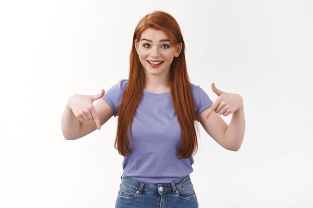 ウエストアップショット感動と興奮の幸せな笑顔の赤毛の女性、紫色のtシャツで立っている白い壁の笑顔、下向き、招待参照、チェックアウトプロモーションバナー、リンクをお勧めします