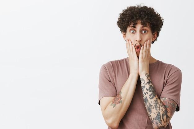Inquadratura dalla vita di un giovane ragazzo moderno creativo e artistico impressionato con tatuaggi acconciatura ricci e baffi che stringono la faccia, piegando le labbra per lo stupore e lo shock senza parole per le notizie scioccanti