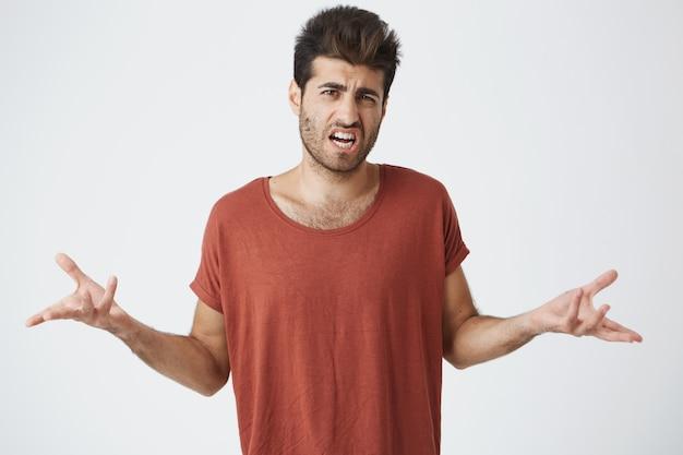 Mezzo busto di irritato giovane in maglietta rossa, acconciatura alla moda gesticolano con le mani arrabbiarsi litigando con il migliore amico. linguaggio del corpo