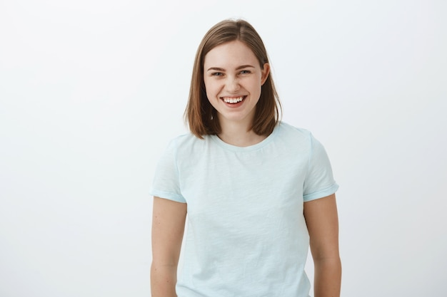 Waist-up shot of joyful entertained and amused good-looking ordinary brunette girl in trendy t-shirt laughing happily and gazing having amusing funny talk with friends over gray wall