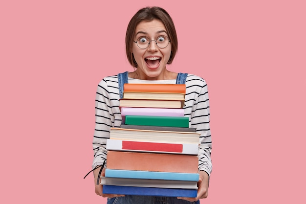 Waist up shot of joyful student in round spectacles, holds pile of books, prepares for seminar or writing report
