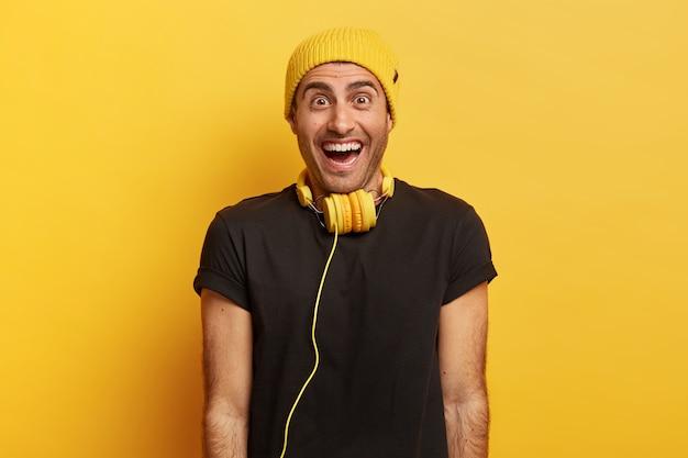 La vita in su di un uomo gioioso e ottimista sorride ampiamente, ha una reazione felice su una piacevole sorpresa