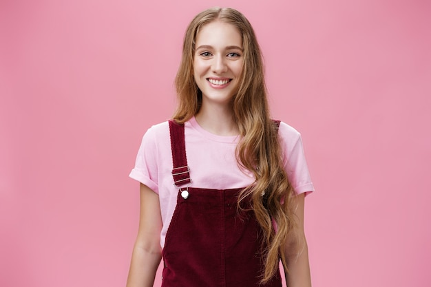 Waist-up shot of kind friendly-looking pleasant young female student with long wavy fair hair in trendy overalls wearing makeup smiling joyfully and gazing at camera with good mood over pink wall.