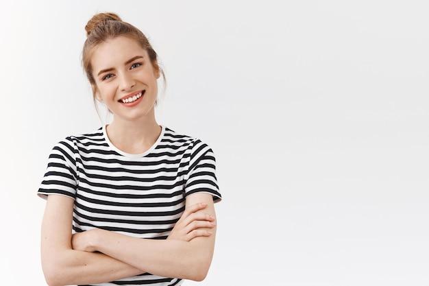 ウエストアップショット幸運な、自信を持って見栄えの良い女性、縞模様のtシャツ、クロスハンドチェスト、ティルトヘッド、プロのように見える笑顔、自信と励ましの乱雑なパン