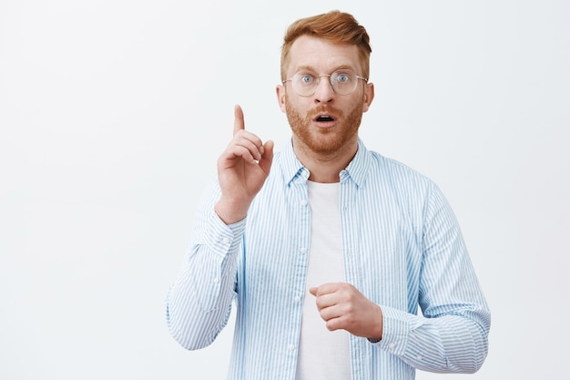 Waist-up shot of man got great idea or plan, raising index finger in eureka gesture, gasping and opening mouth being under impression, giving great suggestion or advice, solving puzzle over grey wall