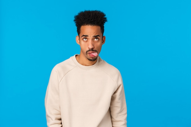 Waist-up shot moody and home-sick handsome african-american guy fooling around, feeling bored and unamused showing tongue, grimacing rolling eyes up, standing blue wall careless