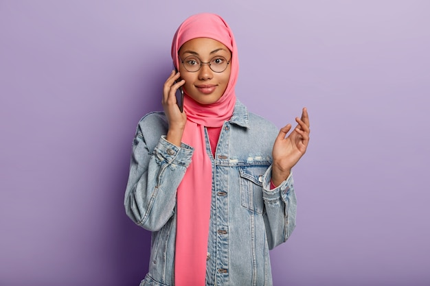 Waist up shot of muslim female enjoys smartphone conversation, being advnaced user of modern device, wears pink hijab and denim jacket, uses public internet connection, isolated on purple wall