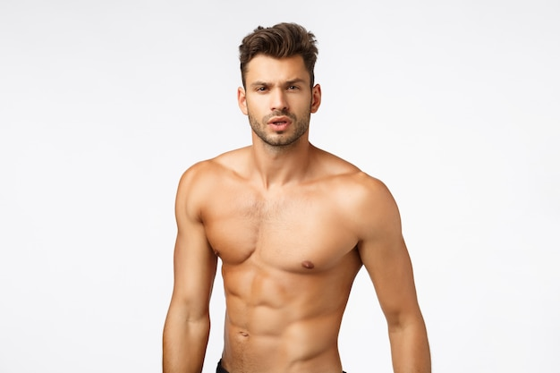 Waist-up shot naked handsome, sexy athlete, sportsman with bare torso, six-pack