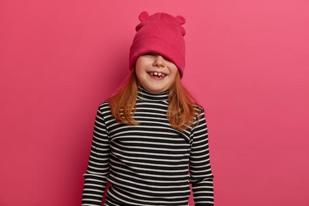 愛らしい女の子のウエストアップショットは、遊び心のあるムードを持ち、帽子の上から見て、愚かで、縞模様のタートルネックを着て、広いスマイルを持ち、バラ色の壁にポーズをとり、不従順またはいたずらです