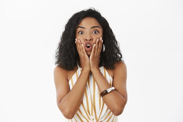 Фото изумленной девушки, которая говорит, что имао взволнован и шокирован, касается лица ладонями, складывая губы