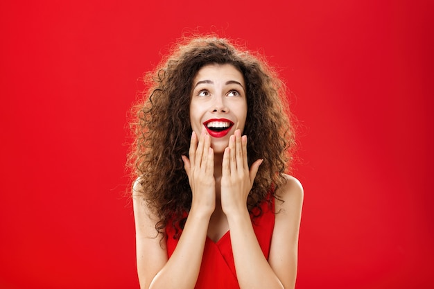 턱에 손바닥을 대고 입을 벌리고 붉은 벽 너머의 기적을 보는 것처럼 기뻐하는 듯한 환하고 즐거운 젊은 꿈꾸는 여자 친구의 웨이스트 업 샷.